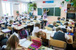 schoolchildren sit at their desks in elementary school